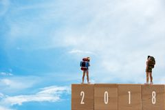 Miniature group traveler standing on wooden 2018 with new year, blue sky background. royalty free stock photo