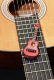 Miniature guitar on acoustic guitar Stock Photos