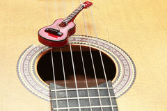 Miniature guitar on acoustic guitar strings Stock Photo