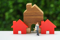Miniature happy couple family standing with wooden house as prop stock images