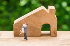 Miniature happy couple family standing with wooden house as prop royalty free stock photography