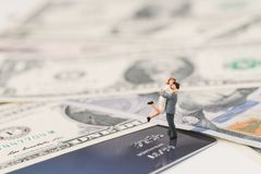 Miniature happy couple holding each other standing on credit card and pile of US Dollar bills, success family financial management stock images