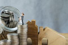 Miniature happy couple standing on stack of coins as property or Stock Image