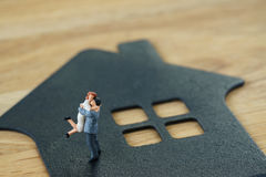 Miniature happy family figure standing on paper house as property or financial investment mortgage plan concept.  royalty free stock photo