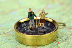 Miniature hikers standing on a compass. Royalty Free Stock Image