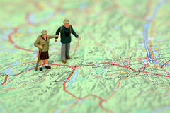 Miniature hikers standing on a map. royalty free stock photos