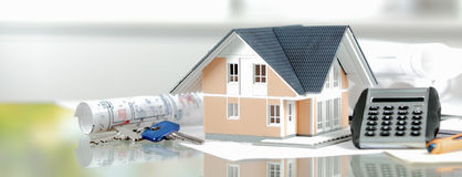 Miniature Home with Keys, Calculator and Blueprint. Real Estate Concept - Miniature Model House on Top of a Glass Table with Calculator, Keys and Blueprint Royalty Free Stock Image