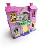 Miniature house. Close-up of toy miniature pink house model on white background with american dollars attached to it Stock Photos