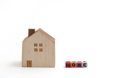 Miniature house with alphabet blocks that spell home. Stock Photos