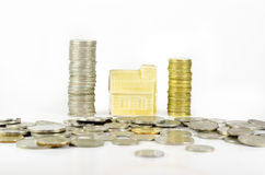 Miniature house behind scattered coins, isolated on white background Royalty Free Stock Photography