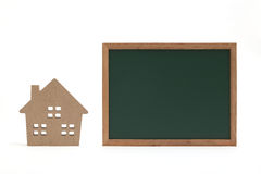 Miniature house and blackboard on white background. Royalty Free Stock Image