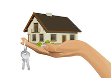 Miniature house building on hand with keys Stock Photography