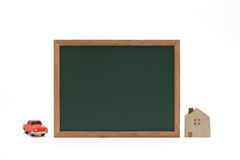 Miniature house, car, and blackboard on white background. Stock Photos