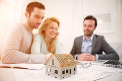 Miniature house in a desk of real estate agent with couple Royalty Free Stock Images