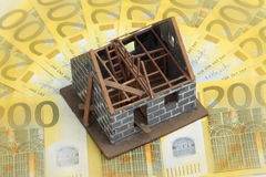 Miniature house on Euro bills. Maintenance and refurbishment costs: miniature houe on Euro bills Royalty Free Stock Photo