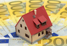 Miniature house on Euro bills. Private housing costs: miniature house on Euro bills Royalty Free Stock Photography
