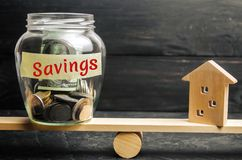 Miniature house and glass jar with coins on the scales. The inscription `savings`. The accumulation of money to buy a house, apart stock images