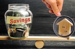 Miniature house and glass jar with coins on the scales. The inscription `savings`. The accumulation of money to buy a house, apart royalty free stock images