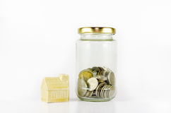 Miniature house beside glass jar filled with coins isolated on white background. Stock Photos