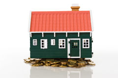Miniature house on golden coins pile Royalty Free Stock Photography