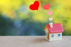 Miniature house with heart sign and blur light bokeh ,love family concept. Miniature house with heart sign and blur light bokeh ,love family stock photo