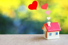 Miniature house with heart sign and blur light bokeh ,love family. Concept stock image