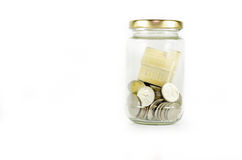 Miniature house inside glass jar filled with coins isolated on white background. Stock Photo