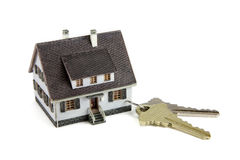 Miniature house on key ring. Concept images of a miniature house connected to a key ring with house keys. White background royalty free stock photo