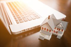 Miniature House And Laptop Computer Resting on Desktop. Miniature House with Laptop Computer Resting on Desktop Stock Photos