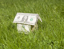 Miniature house made of dollar. A miniature house made of dollar bills outside in the grass Stock Images