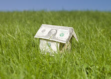 A miniature house made of dollar bills. Outside in the grass Stock Images
