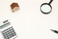 Miniature house, magnifying glass, calculator on blank notebook. New house concept royalty free stock image