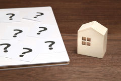 Miniature house and many question marks on white papers.   House with question marks. Royalty Free Stock Photo