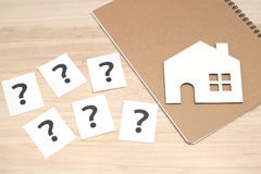 Miniature house and many question marks on white papers.   House with question marks. Stock Image