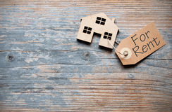 Miniature house with rental label. Small house with rental label over a wooden background with space Stock Image
