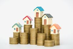 Miniature house on stack coins using as property and business concep, isolated on white background stock photo