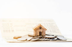 Miniature house stand on the stack of coins on book bank. Miniature house stand on the stack of coins on book bank background with light. Financial for house stock photos