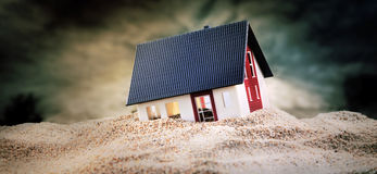 Miniature of house standing in sand. Miniature of house standing in pile of sand royalty free stock image