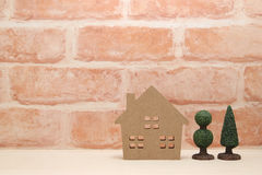 Miniature house and trees in front of brick wall. Royalty Free Stock Photos