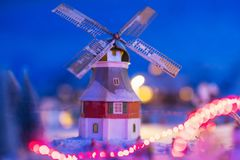 Miniature house with windmill in winter. Miniature houses with windmill in the village with snow at night with light up decoration. Christmas winter model for Stock Image