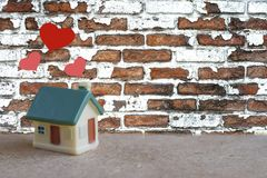 Miniature House With Heart Sign And Blur Brick Wall Background ,love Family Concept Stock Image