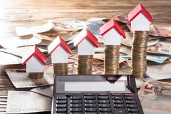 Miniature Houses Resting On Increasing Coin Stack. With Calculator On Euro Notes Stock Photos