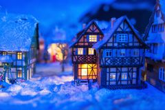 Miniature houses in village at winter. Miniature houses in the village covered by snow at night with light up decoration. Christmas winter model for holiday Stock Photography