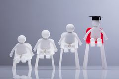 Human Figures Sitting On White And Red Chairs. Miniature Human Figures Sitting On Increasing Scale Of White And Red Chairs In A Row royalty free stock photo
