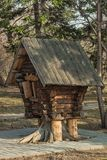 Miniature hut in the city park. Park zone. A tiny log house in the form of a small hut among trees Royalty Free Stock Image