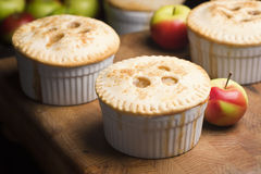 Miniature Individual Apple Pies. Individual sized apple pies on a wooden board with apples in the background stock images