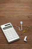 Miniature items of illness or injury beside calculator. Stock Photos
