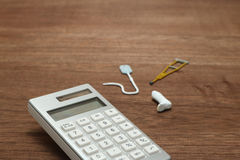 Miniature items of illness or injury beside calculator. Royalty Free Stock Photo