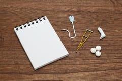 Miniature items of illness or injury beside memo pad. Royalty Free Stock Image