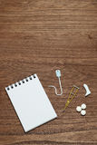 Miniature items of illness or injury beside memo pad. Stock Image